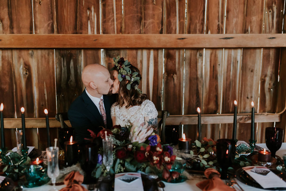 Bride in flower crown with tattoo sleeve and groom sit at a styled table with black tapers burning bright. Shot at The Barn at Wagon Wheel Farm.