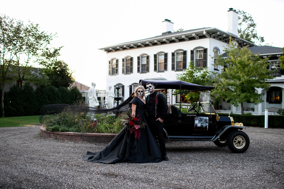 The bride and groom stand before their carriage at Maxwell Mansion in their Halloween wedding attire.