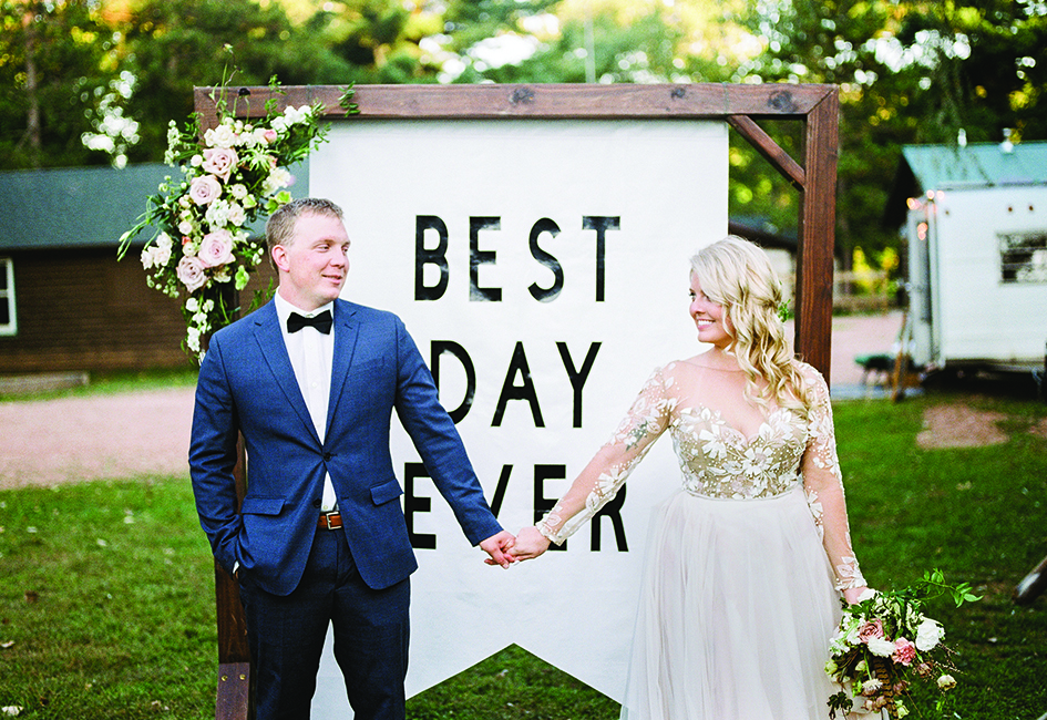 Ashley Zelenka and Evan Bohman hold hands in front of a Best Day Ever sign at their rustic camp wedding.