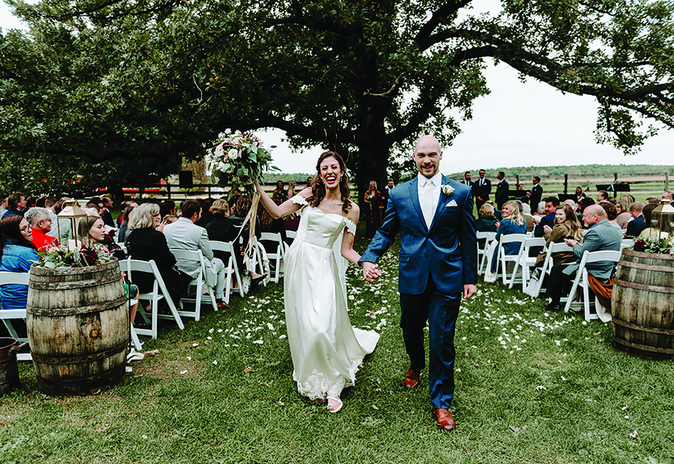 Caroline Grassl and Miles Groeschel walk down the aisle at their Sugarland Barn wedding.
