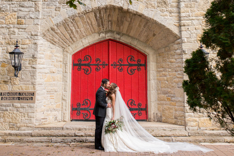 The couple embraces outside the historic stone church at St. John's Military Academy