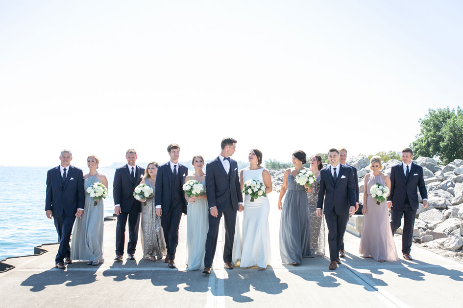The bridal party stands along the water of Lake Michigan for their portraits