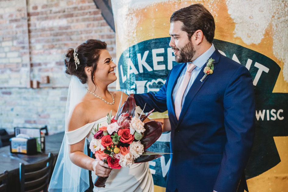 The bride, holding her homemade bouquet, with the groom at Lakefront Brewing in Milwaukee
