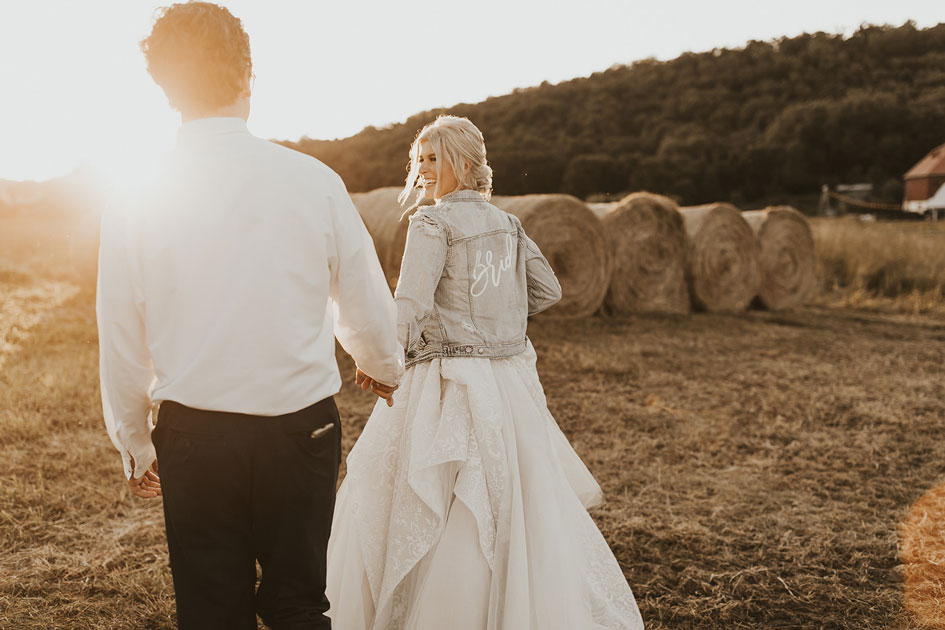 The bride shows her down-home style in a distressed and embellished bridal jean jacket.