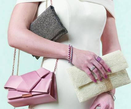 A bride holds three different bridal clutches: pewter, pink and ivory.