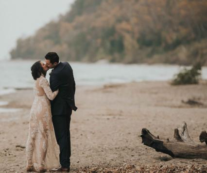 The bride, wearing Free People, kisses her groom on the beach at Grant Park
