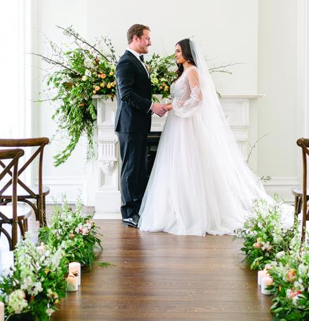 A bride and groom stand in the aisle at the Covenant at Murray Mansion amid their orange, gold and peach wedding flowers