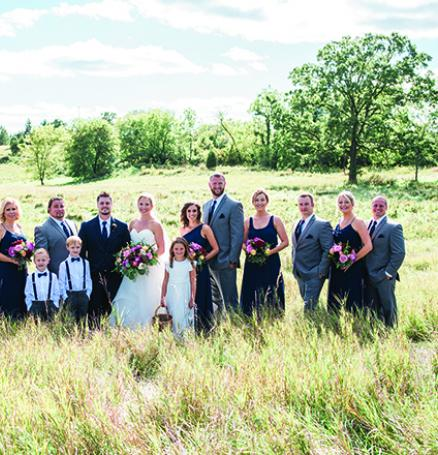 Carrie Seibel and Zach Fisher with their wedding party at St. Anthony on the Lake.