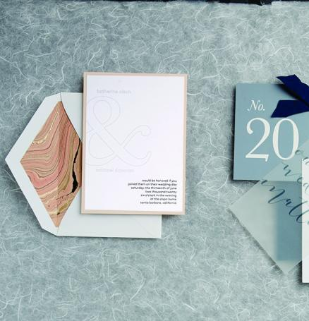 Two wedding invitations, one featuring embossed names and a marbled design and the other featuring a vellum overlay and the wedding hashtag