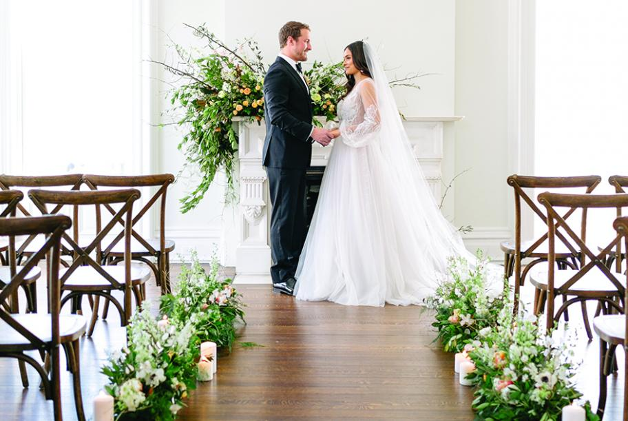 A bride and groom stand in the aisle at the Covenant at Murray Mansion amid their orange, gold and peach wedding flowers.