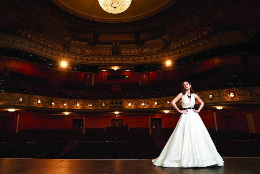 A bride stands on stage modeling a Legends Romona Keveza style No. L7171 silk shantung taffeta ballgown with pleated halter from White Dress Bridal Boutique.