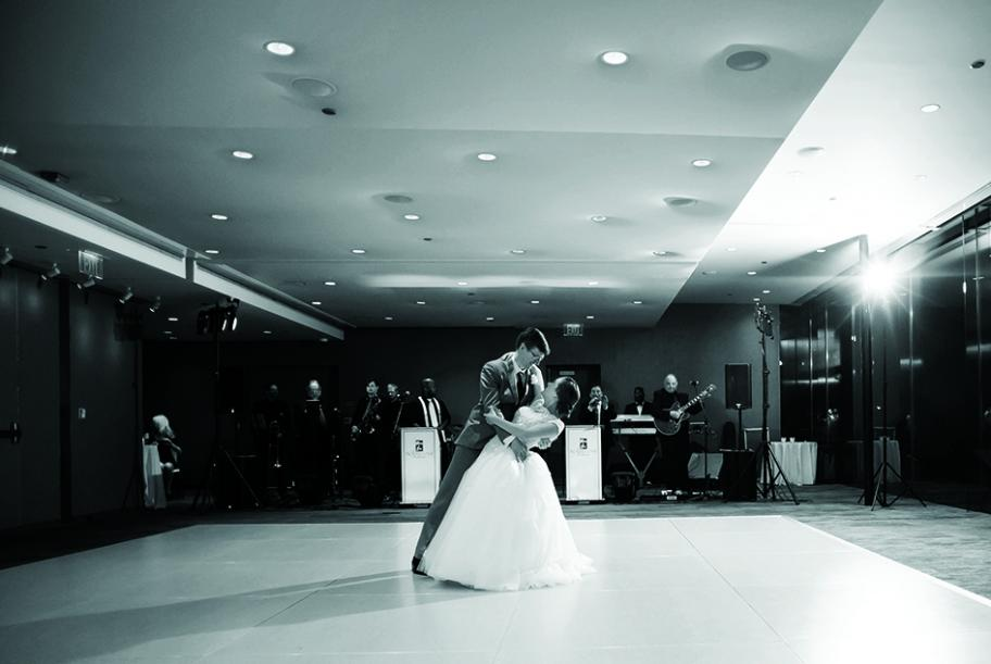 A couple performs their first dance at their wedding while a band plays in the background.