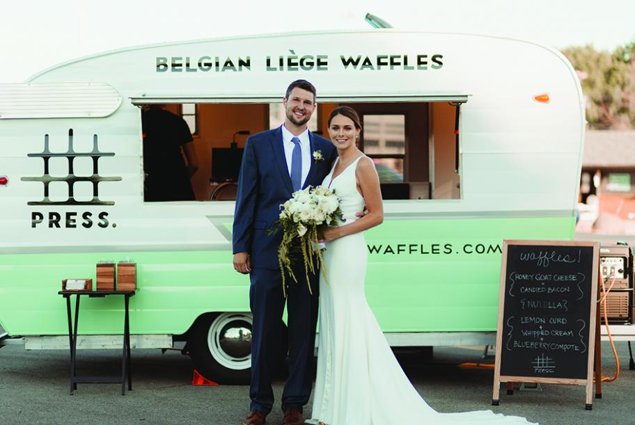 A couple stands in front of Belgian Liege Waffles, part of a new wedding trend: food stations.
