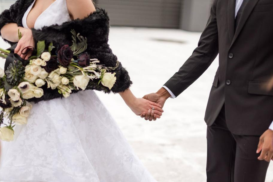 The bride and groom hold hands on a snow-covered rooftop accompanied by a stunning bouquet.