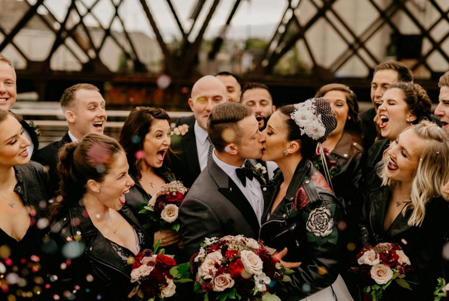 The bridal party looks on as the couple kisses near a bridge