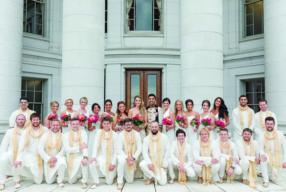 Molly Stiffler and Bobby Syal pose with their wedding parties. The groom and groomsmen wear traditional Indian dress.