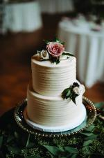 A two-tier white wedding cake with floral decorations.