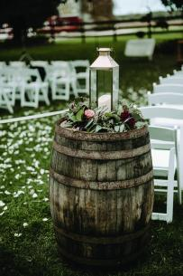 A lantern and floral decoration sit on a barrel at this Sugarland Barn wedding.