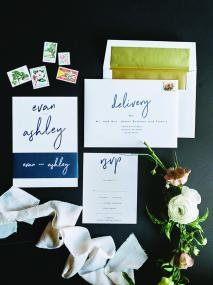 A details photo featuring blue and gold wedding invites and floral stamps.