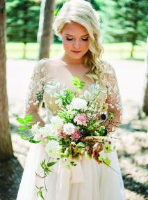 Ashley Zelenka holds her bouquet at her rustic camp wedding.