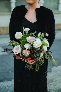 A bridesmaid holds a pink and white bouquet.