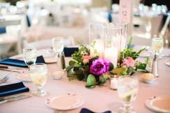 A short floral centerpiece with candles.