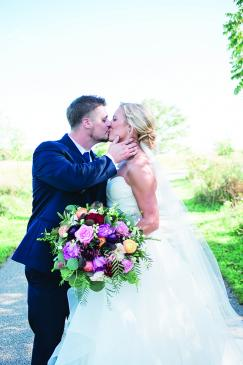Carrie Seibel and Zach Fisher kiss at their St. Anthony on the Lake wedding.