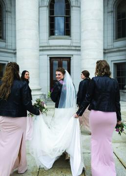 Jayme Udvare looks back at the camera as she and her bridesmaids walk forward, clad in leather dresses.