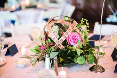 A golden centerpiece with pink floral accents.