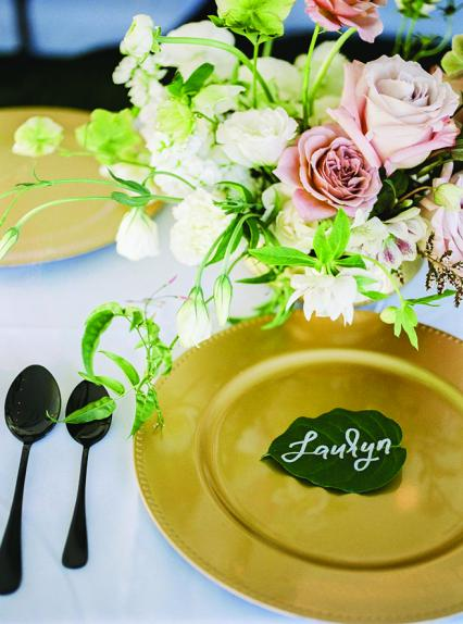 A gold plate and floral centerpiece on the table at Ashley Zelenka and Evan Bohman's rustic camp wedding.