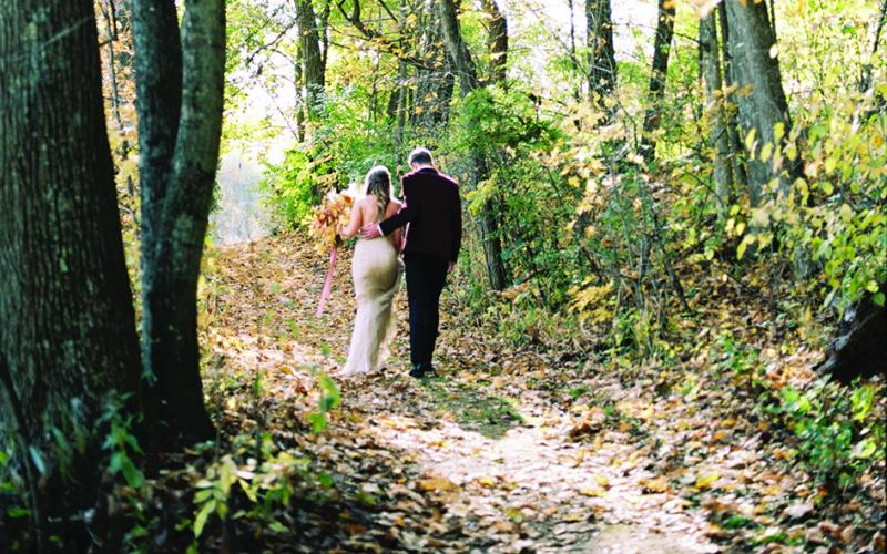A bride and groom walk a path at the golden hour. His burgundy suit and her neutral wedding dress complement the fall wedding theme.